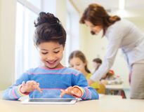 Little school girl with tablet pc over classroom Stock Photos