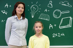 Little school girl with teacher at blackboard Royalty Free Stock Photos