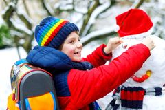 Little school kid boy in colorful clothes, with glasses and backpack having fun with snowman after elementary school end stock photo