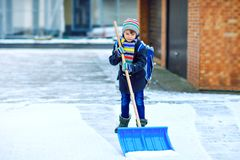 Little school kid boy of elementary class cleaning snow with shovel before going to school. Happy child having fun with stock photos