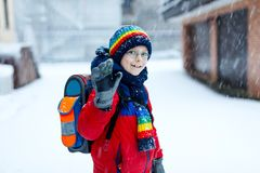 Happy kid boy with glasses having fun with snow on way to school, elementary class Royalty Free Stock Images