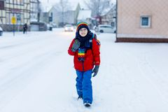 Happy kid boy with glasses having fun with snow on way to school, elementary class Royalty Free Stock Photo