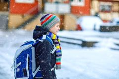 Little school kid boy of elementary class walking to school during snowfall. Happy child having fun and playing with stock images