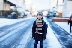 Little school kid boy of elementary class walking to school during snowfall. Happy child having fun and playing with royalty free stock photos