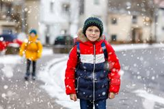 Little school kid boy of elementary class walking to school during snowfall. Happy child and student with eye glasses royalty free stock photo