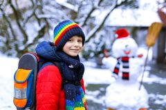 Happy kid boy with glasses having fun with snow on way to school, elementary class Stock Image