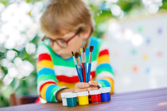 Little school kid boy with glasses holding lots of brushes and c Royalty Free Stock Images