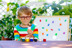 Little school kid boy with glasses holding lots of brushes and c Stock Photos