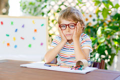 Little school kid boy with glasses holding wax crayons Stock Photo