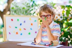 Little school kid boy with glasses holding wax crayons Royalty Free Stock Photos