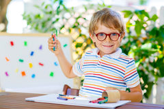 Little school kid boy with glasses holding wax crayons Stock Image