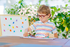 Little school kid boy with glasses holding wax crayons Royalty Free Stock Photography