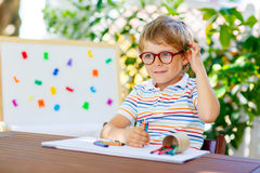 Little school kid boy with glasses holding wax crayons Stock Photography