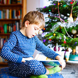 Little school kid boy reading a book on Christmas Stock Photo
