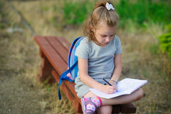 Little school miss sits having crossed legs on a park bench and something diligently writes in the notebook. Stock Photo