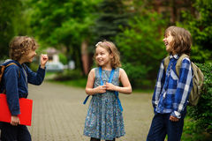 Little school students briskly talk on the schoolyard. Royalty Free Stock Image