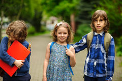 Little school students on the schoolyard. Stock Photos