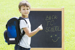 Little schoolboy against the blackboard. Education, Back to school concept Stock Photos