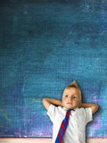Little schoolboy with blackboard. In background Royalty Free Stock Photo