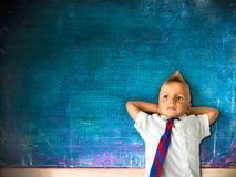 Little schoolboy with blackboard. In background Royalty Free Stock Photos