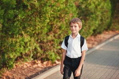 Little schoolboy comes back from school in good mood. The boy goes on a footpath. He has raised eyes to the sky and Stock Images