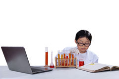 Little schoolboy doing research. Portrait of little schoolboy wearing lab coat and doing research, isolated over white background Stock Photo