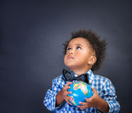 Little schoolboy with globe in hands. Portrait of cute little African boy holding in hands small globe on blackboard background, looking up, back to school Royalty Free Stock Photos