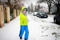 Little schoolboy goes down the street in winter day. Royalty Free Stock Images