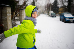 Little schoolboy goes down the street in winter day. Royalty Free Stock Image