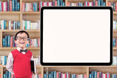 Little schoolboy laughing in library Stock Photo