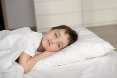 Little schoolboy resting in white bed with eyes open Stock Image