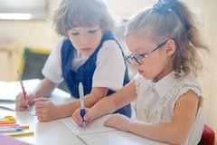 Little schoolboy and schoolgirl diligently doing their homework. Stock Photos