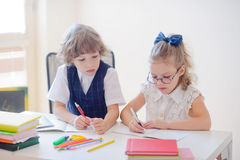 Little schoolboy and schoolgirl diligently doing their homework. Royalty Free Stock Photography