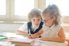 Little schoolboy and schoolgirl diligently doing their homework. Royalty Free Stock Photos