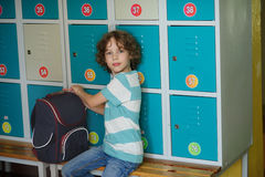 Little schoolboy sitting on the bench near a lockers. Stock Photo
