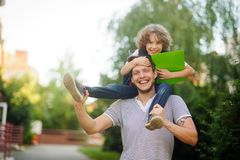 Little schoolboy sitting on the shoulders of father and clings to his head Royalty Free Stock Images
