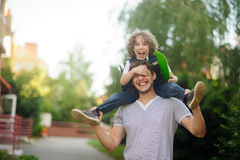 Little schoolboy sitting on the shoulders of his father. Royalty Free Stock Photo