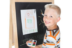 Little schoolboy. Smiling little schoolboy drawing on school board over white Royalty Free Stock Photos