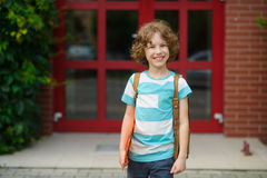 The little schoolboy stand on a schoolyard and joyfully smiles. Stock Images
