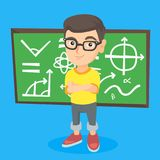 Little schoolboy standing in front of blackboard. Young caucasian schoolboy in glasses standing in front of classroom blackboard. Schoolboy standing with Royalty Free Stock Images