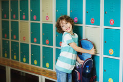 Little schoolboy standing in the hall near the lockers. Stock Photo