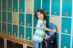 Little schoolboy standing in the hall near the lockers. Royalty Free Stock Images