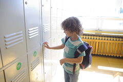 Little schoolboy standing near lockers in school corridor and opens his drawe Royalty Free Stock Photography