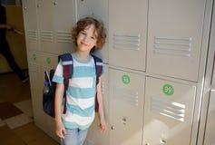 Little schoolboy standing near lockers in school hallway. Royalty Free Stock Image