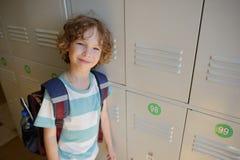 Little schoolboy standing near lockers in school hallway. Royalty Free Stock Photo