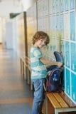 Little schoolboy standing near lockers in school hallway. Stock Photography