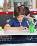 Little Schoolboy Studying At Desk Royalty Free Stock Images