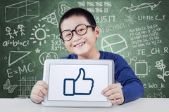 Little schoolboy with thumb up in class. Cute male elementary school student smiling at the camera while showing thumb up on the tablet screen, shot in the Stock Images