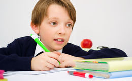 Schoolboy writing homework from school in workbook Royalty Free Stock Images
