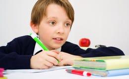 Schoolboy writing homework from school in workbook. Little schoolboy writing homework from school in workbook Royalty Free Stock Images